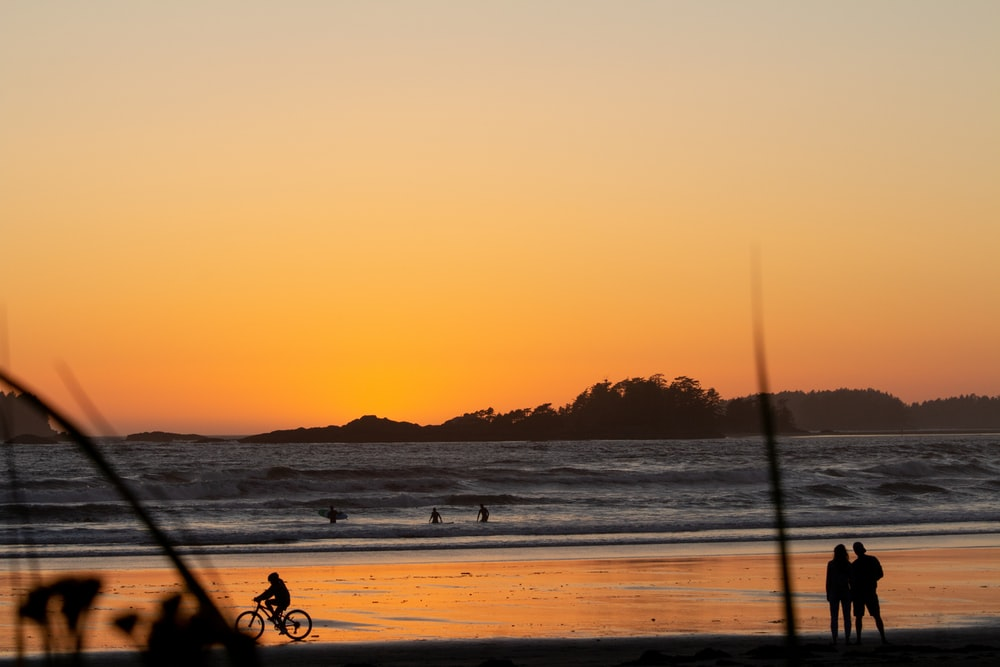 silhouette of person riding bicycle on beach during sunset