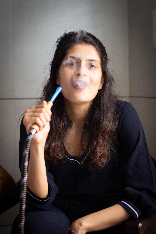 woman in black long sleeve shirt holding black telephone