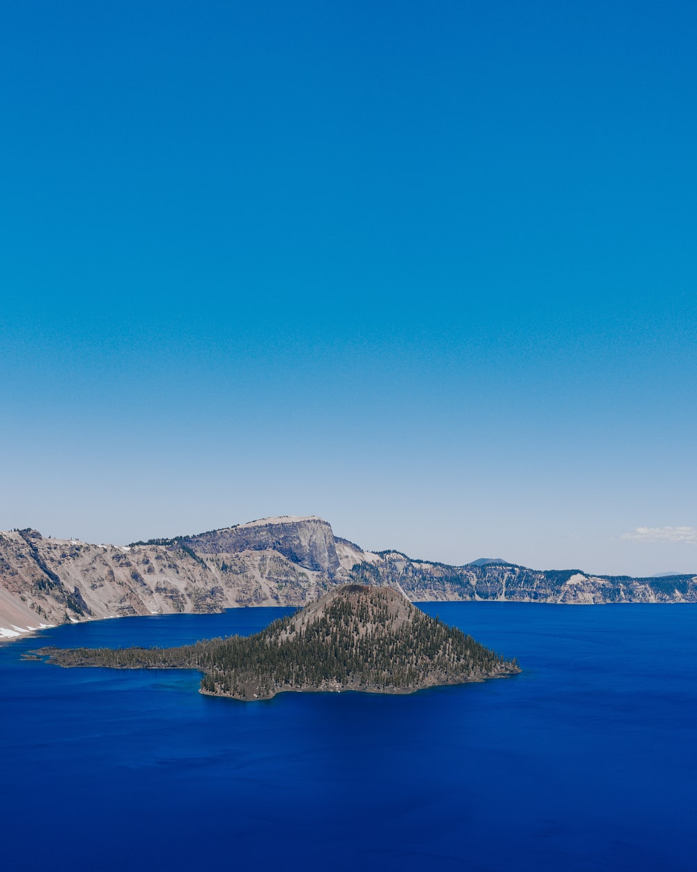 blue sea near mountain under blue sky during daytime