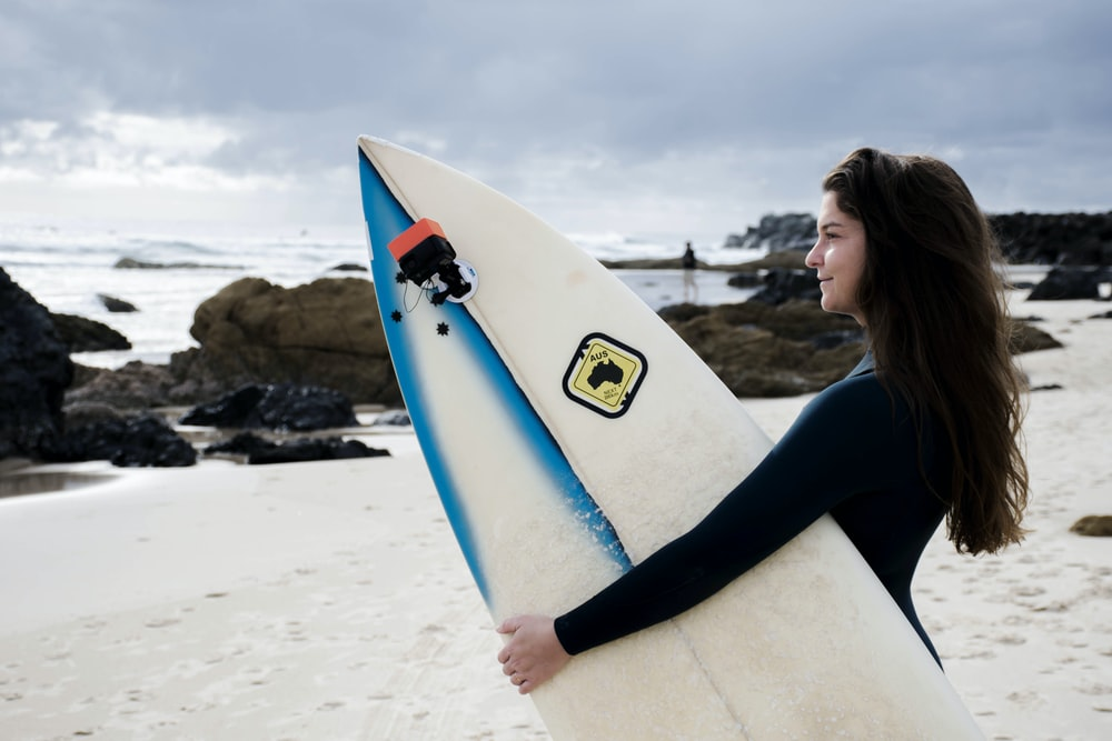 woman in black long sleeve shirt holding white surfboard on beach during daytime