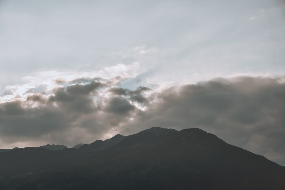 white clouds over mountain during daytime