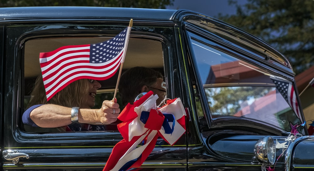 woman in car holding us a flag