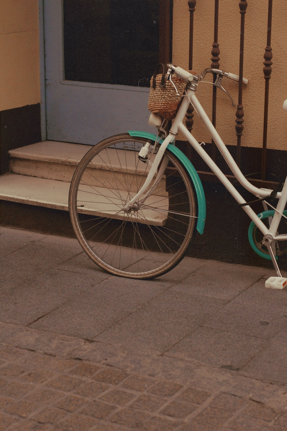 teal city bike parked beside brown concrete wall