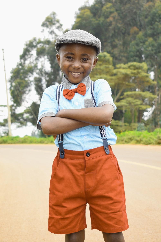boy in orange shorts wearing black hat
