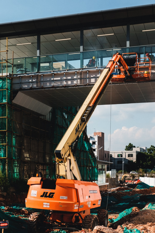 orange and black crane near building during daytime