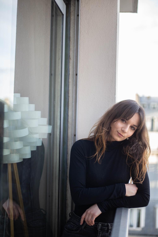 woman in black long sleeve shirt sitting beside glass window