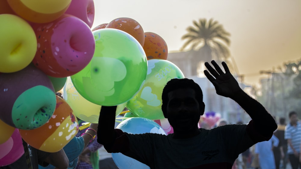 man in blue shirt holding balloons