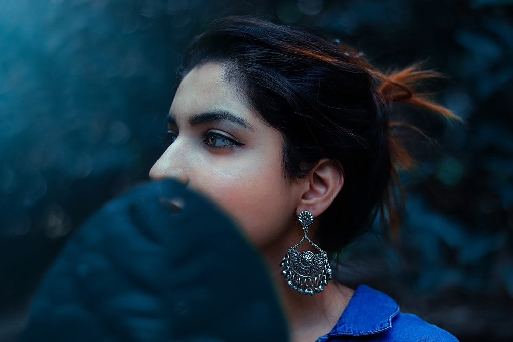 woman in blue shirt wearing silver and diamond drop earrings
