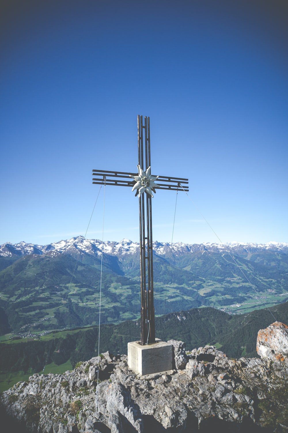 black cross on top of mountain during daytime