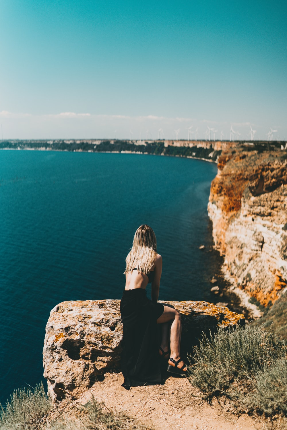 woman in black dress sitting on rock formation looking at the sea during daytime