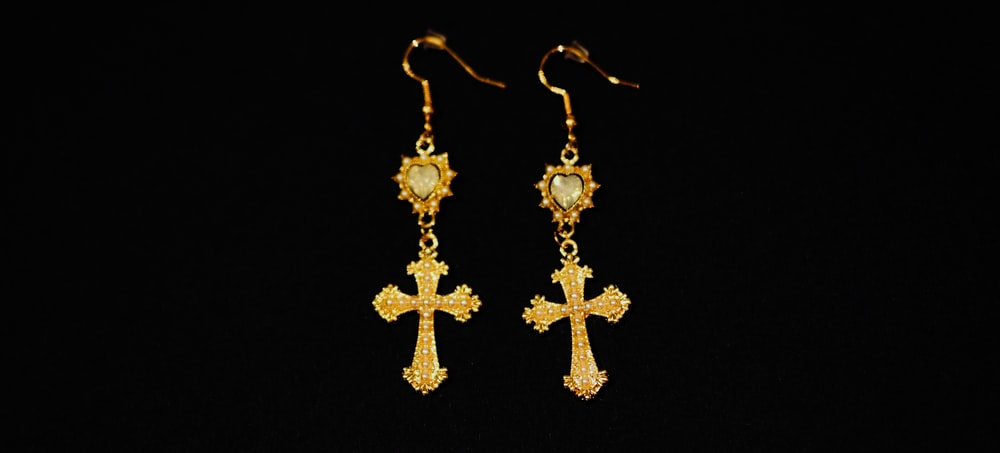 gold cross pendant necklace with black background