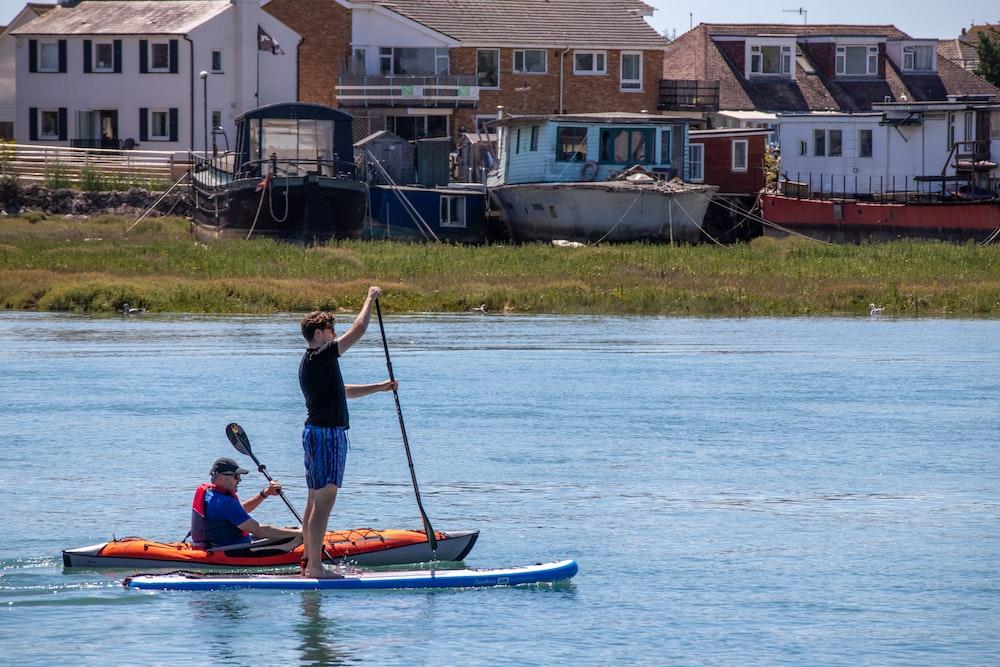 man in blue shirt riding on blue kayak during daytime
