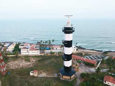 Puducherry white and black lighthouse near body of water during daytime