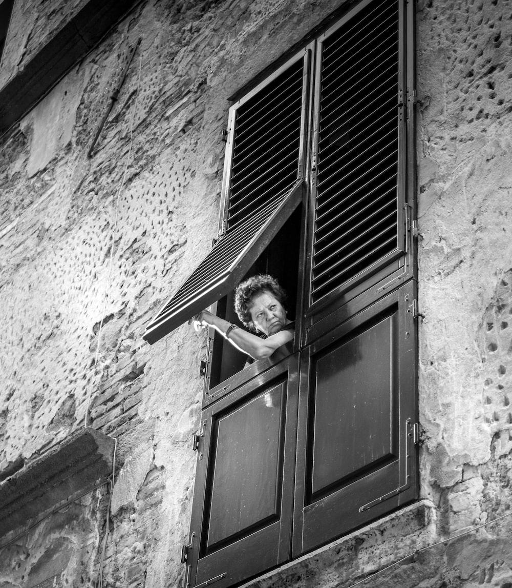 grayscale photo of woman in window