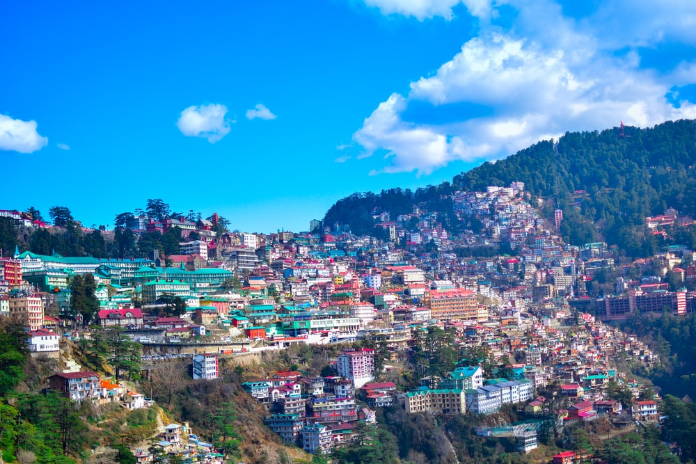 city near mountain under blue sky during daytime