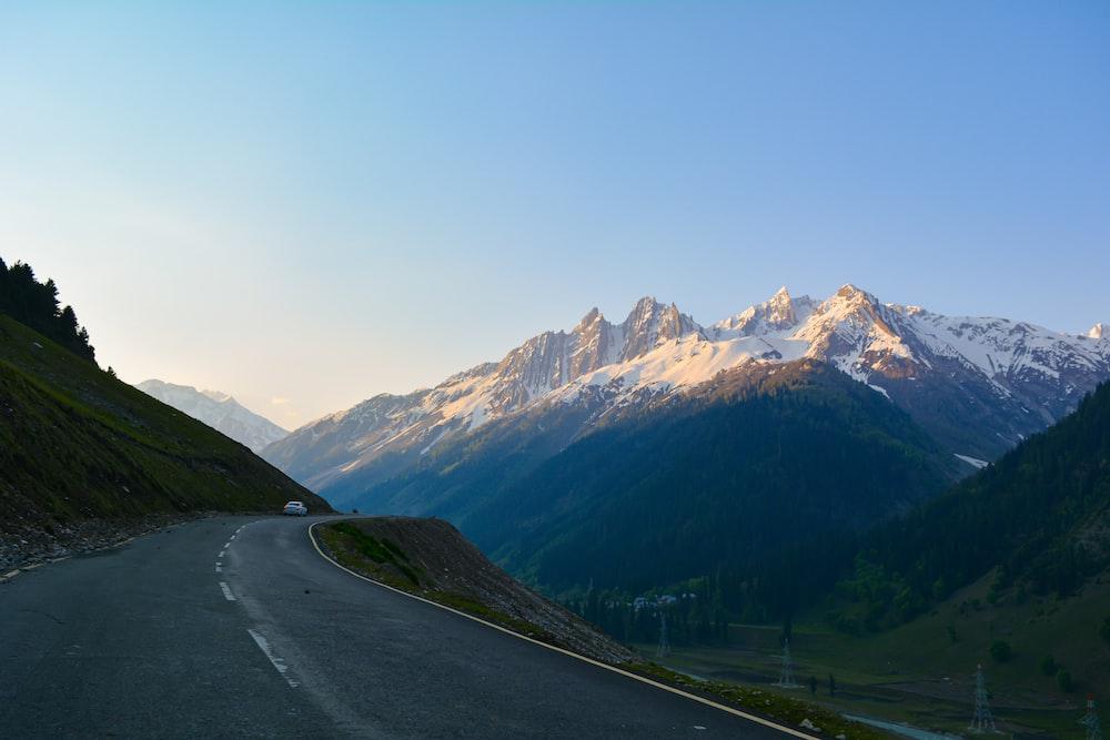 gray asphalt road near green mountains during daytime