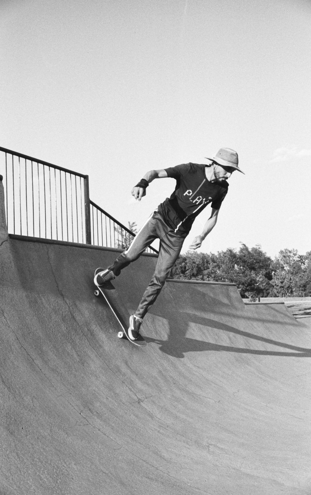 man in black t-shirt and pants riding skateboard in grayscale photography