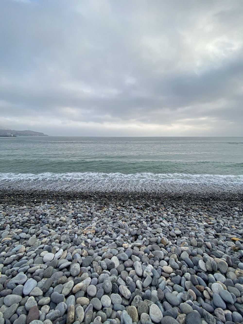gray and white pebbles on seashore under cloudy sky during daytime