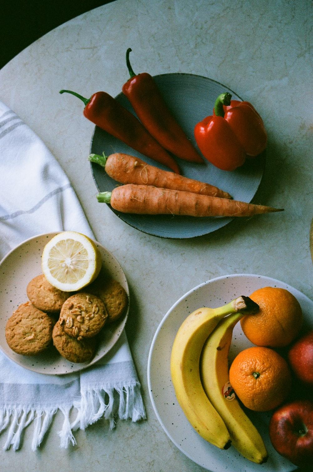 orange and banana fruits on white ceramic plate