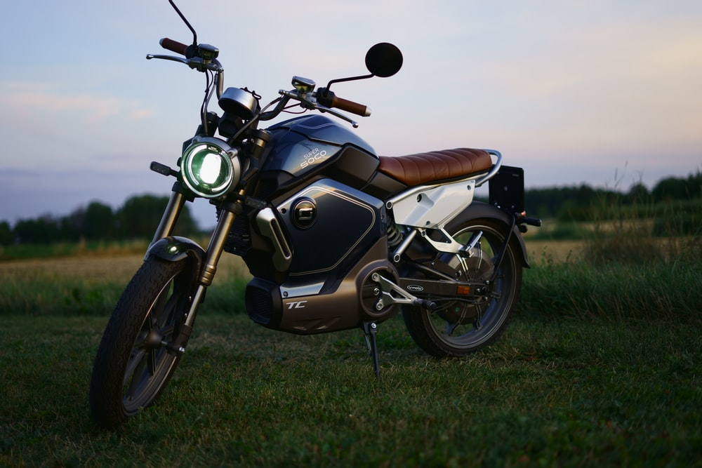 black and brown motorcycle on green grass field during daytime
