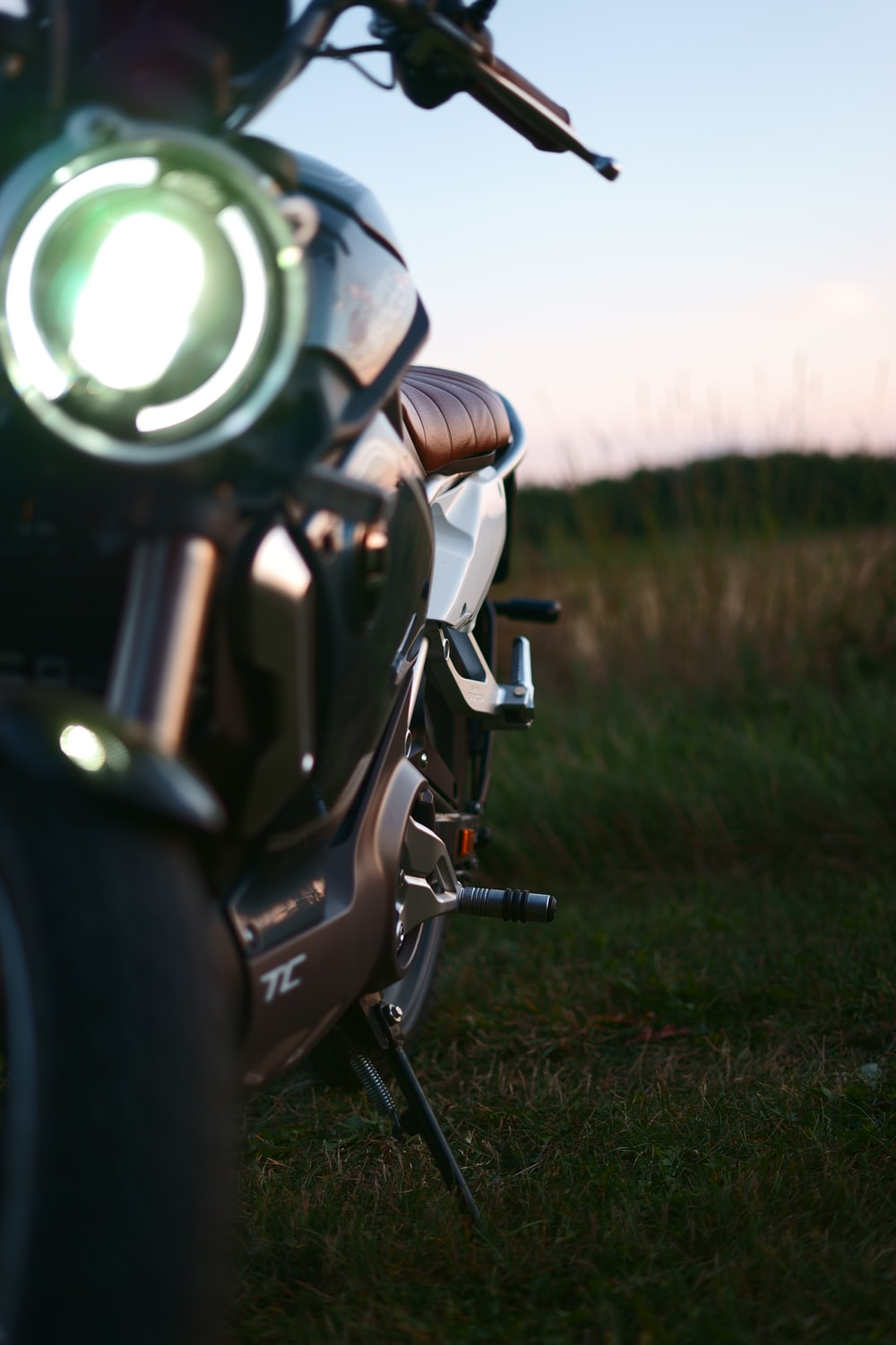 black motorcycle on green grass field during daytime