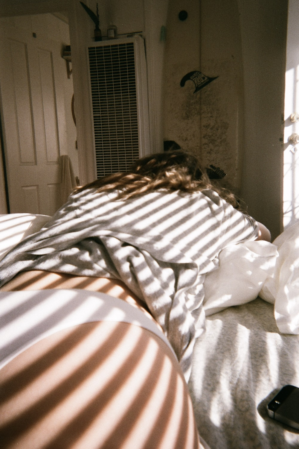person in white and brown shirt lying on bed