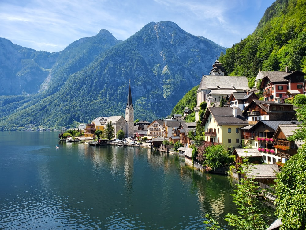 houses near body of water and mountain during daytime