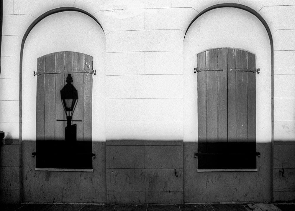 grayscale photo of man standing on window