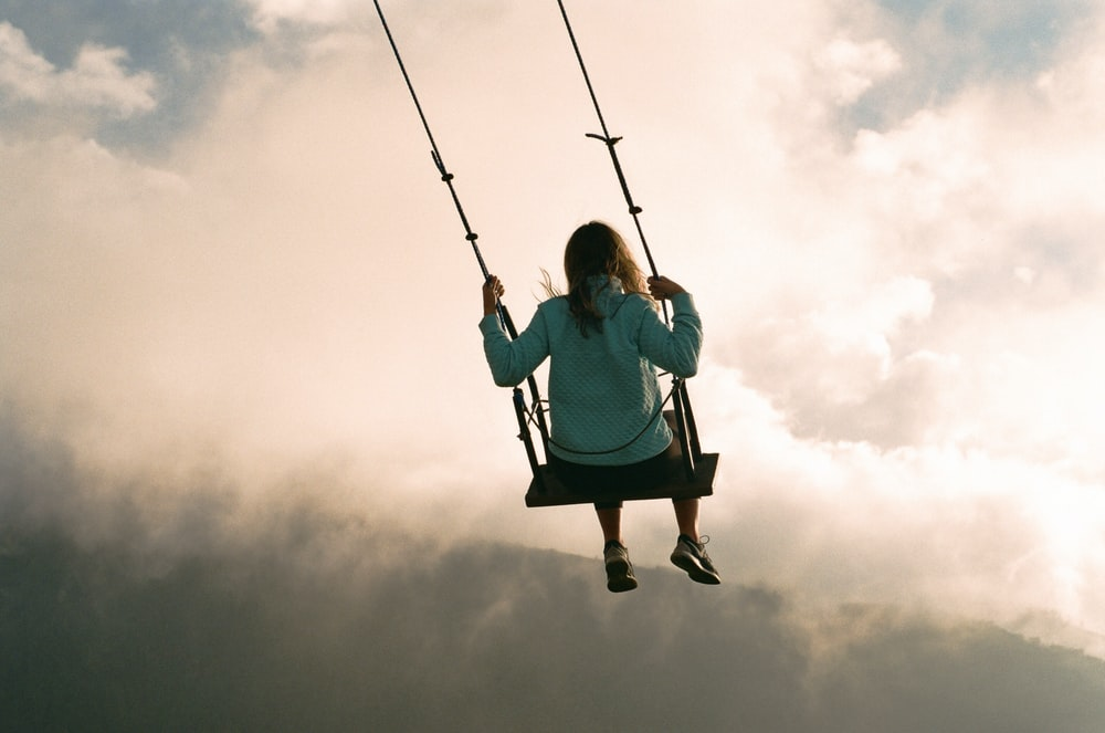 girl in blue hoodie sitting on swing under cloudy sky during daytime