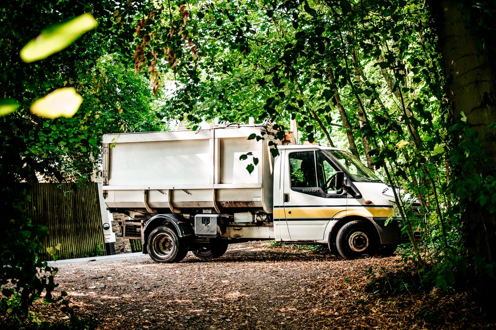 white and green truck on dirt road during daytime