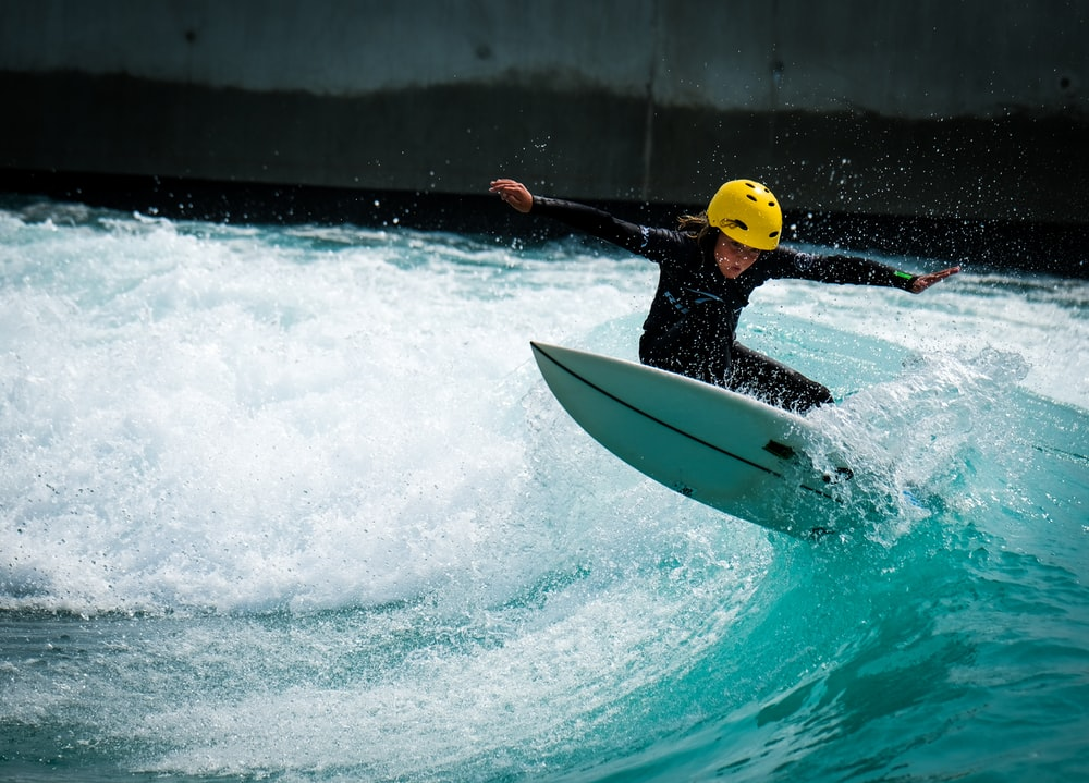man in yellow life vest riding white surfboard during daytime