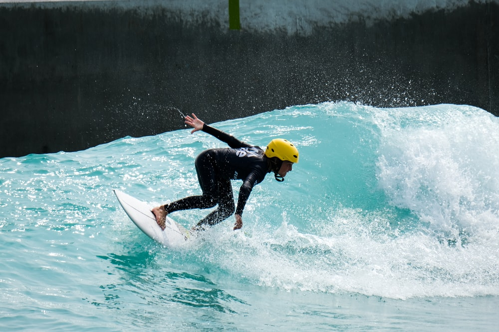 man in black wet suit riding white surfboard during daytime