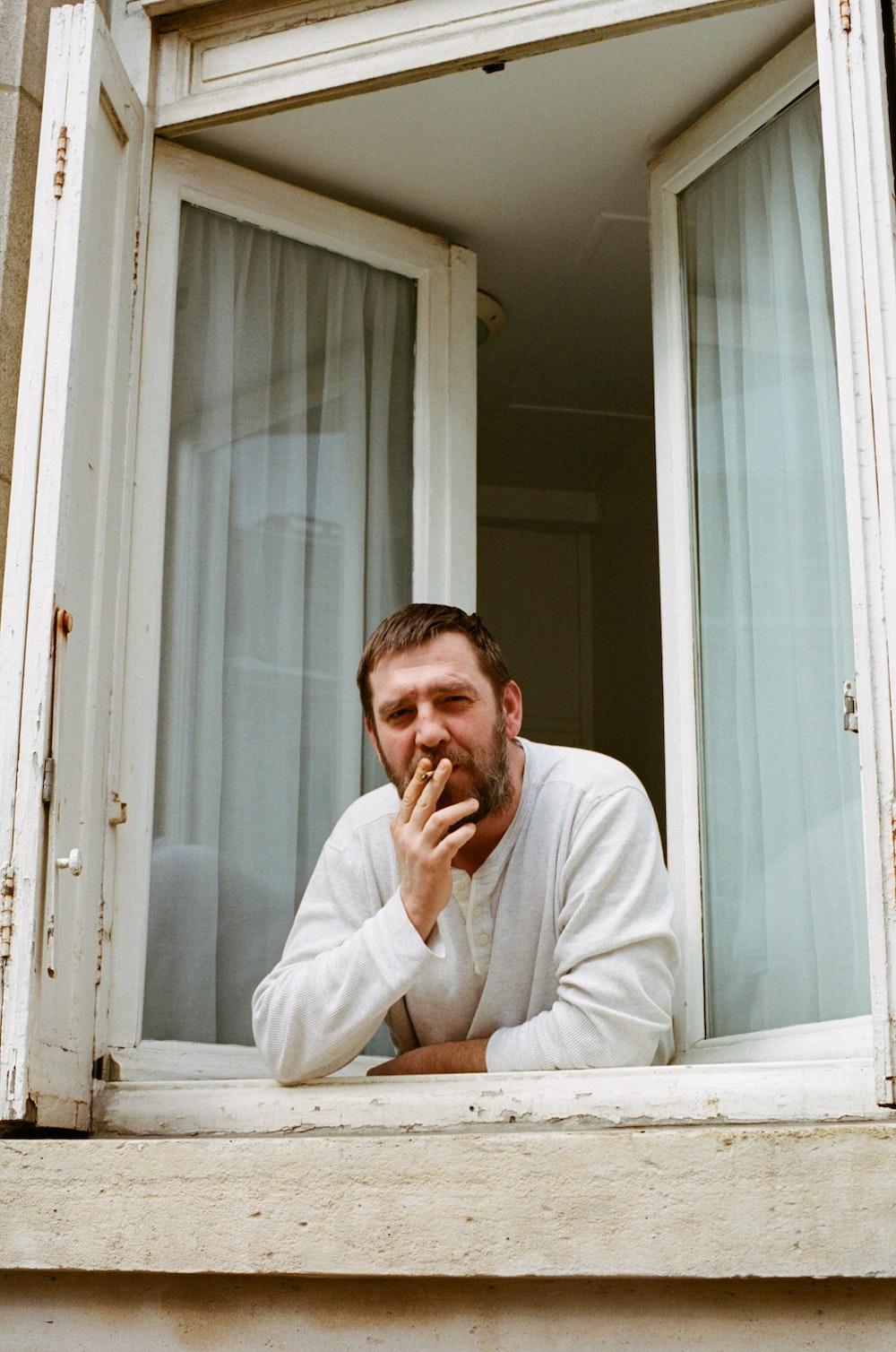 man in white dress shirt sitting beside white wooden framed glass window