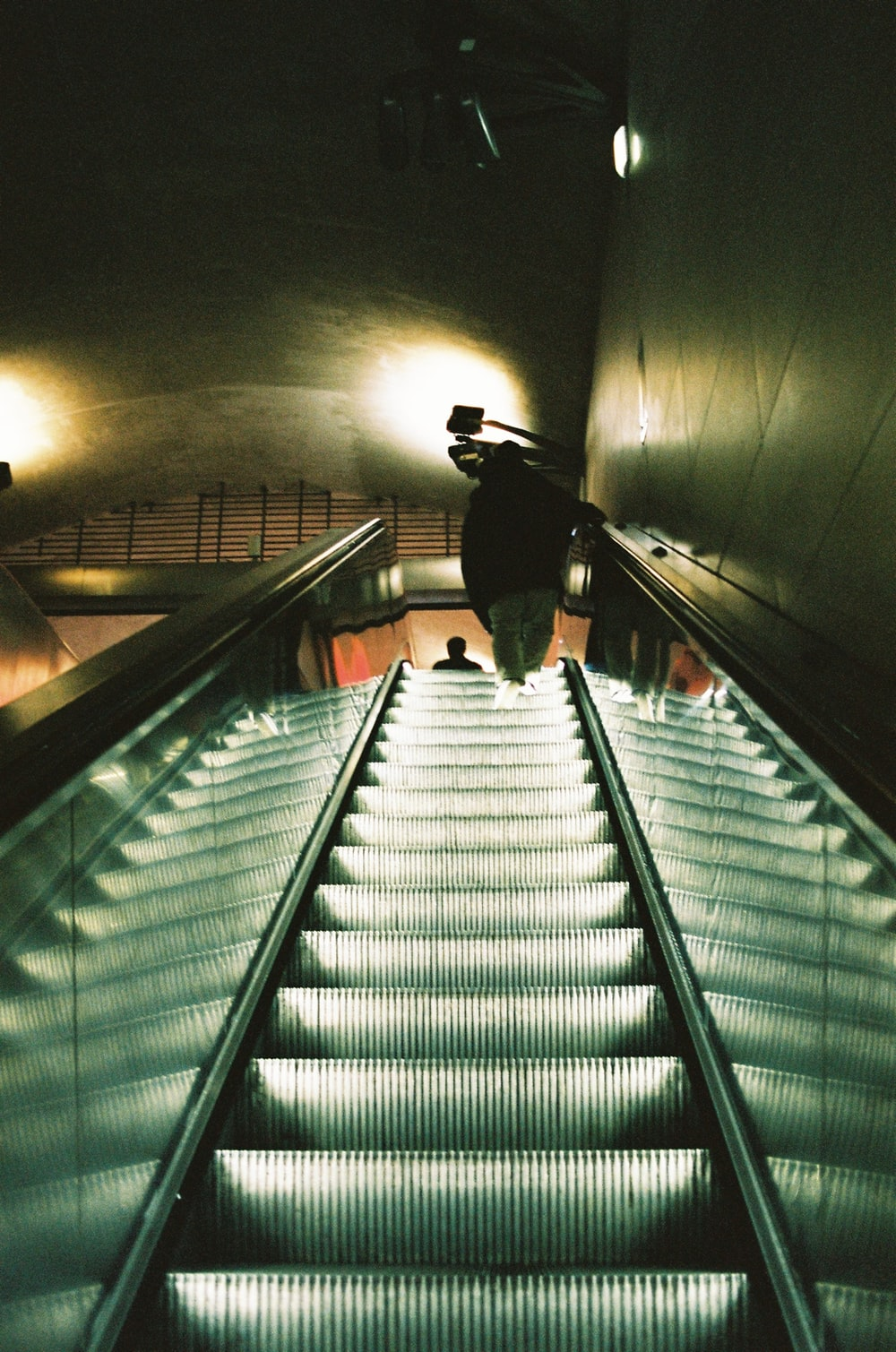 man in black jacket walking on gray staircase