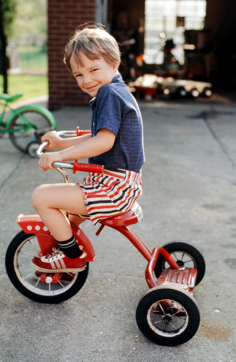 boy in blue and red crew neck t-shirt riding red trike