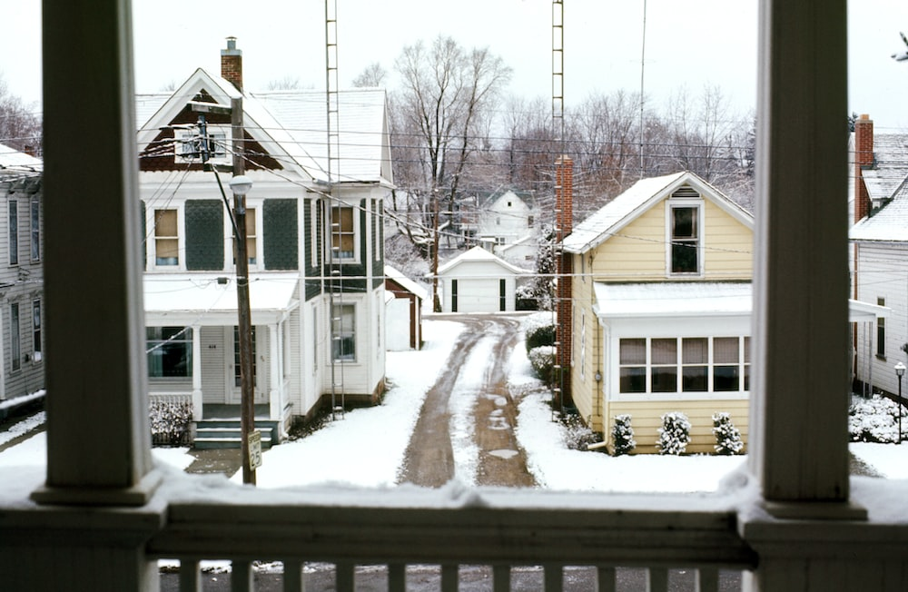white and brown wooden house covered with snow during daytime