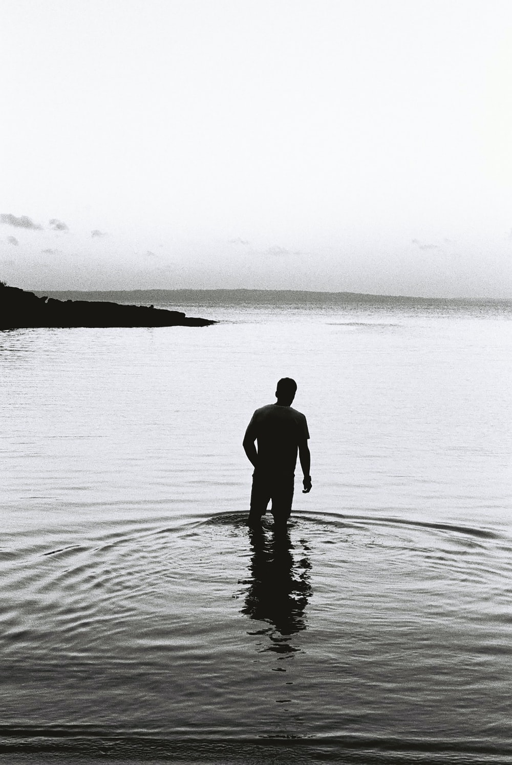 silhouette of man standing on water