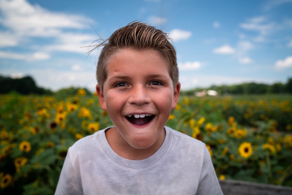 boy in white crew neck shirt standing on yellow flower field during daytime