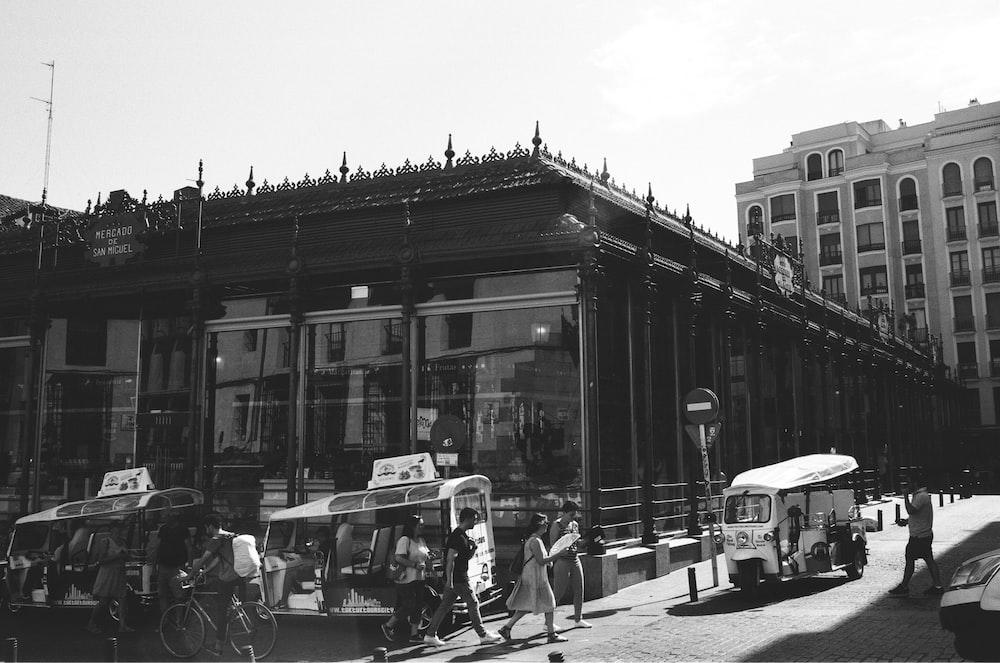 grayscale photo of people walking on street near building