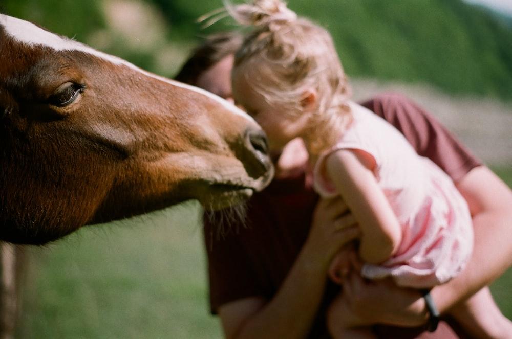 girl in pink jacket feeding brown horse during daytime