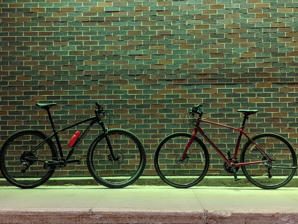 red and black mountain bike leaning on brown brick wall