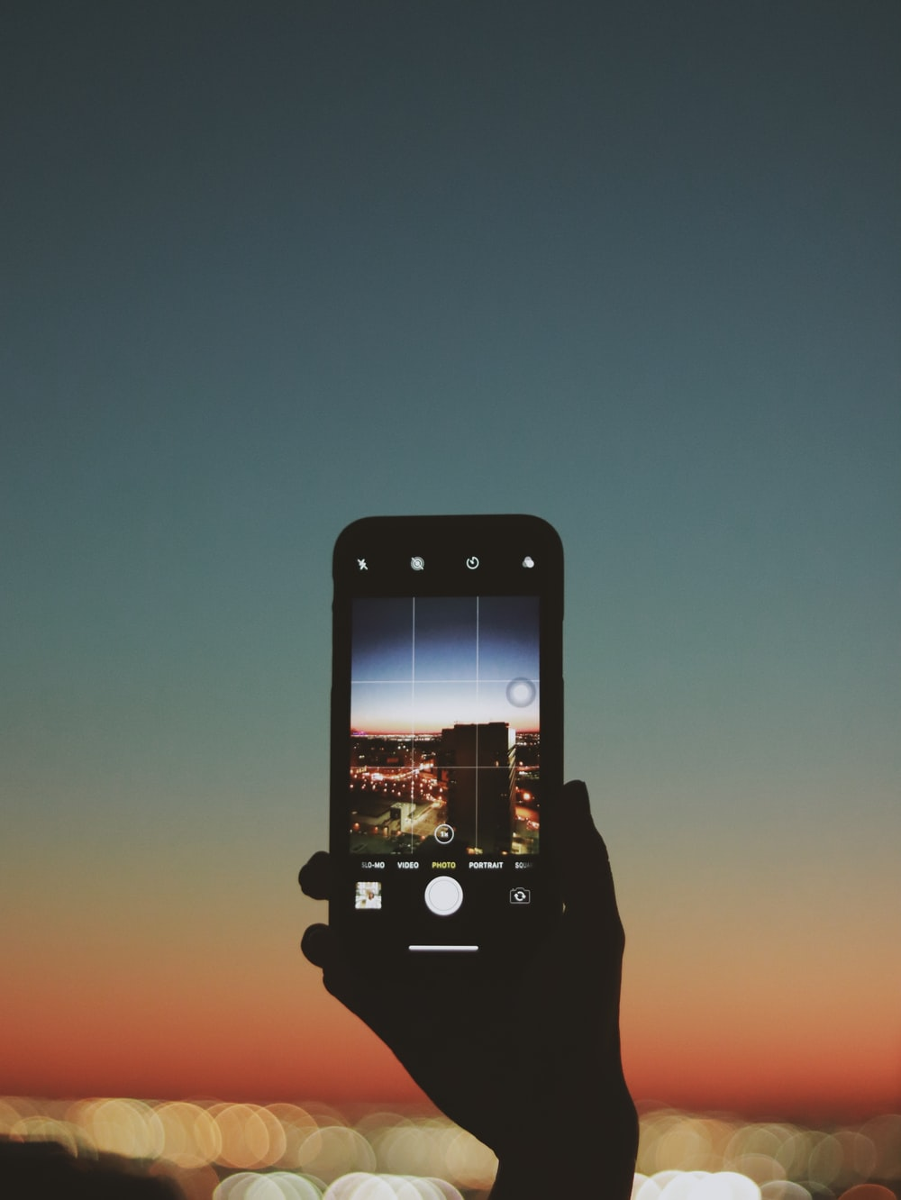 black iphone taking photo of city skyline during night time