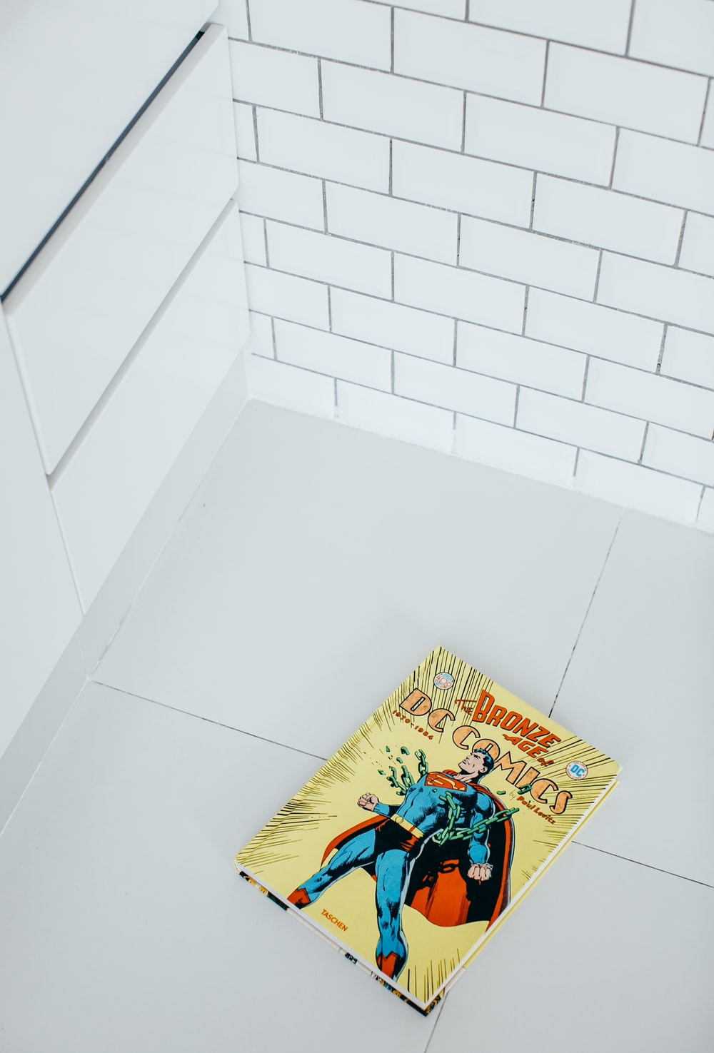 yellow and blue book on white ceramic tile