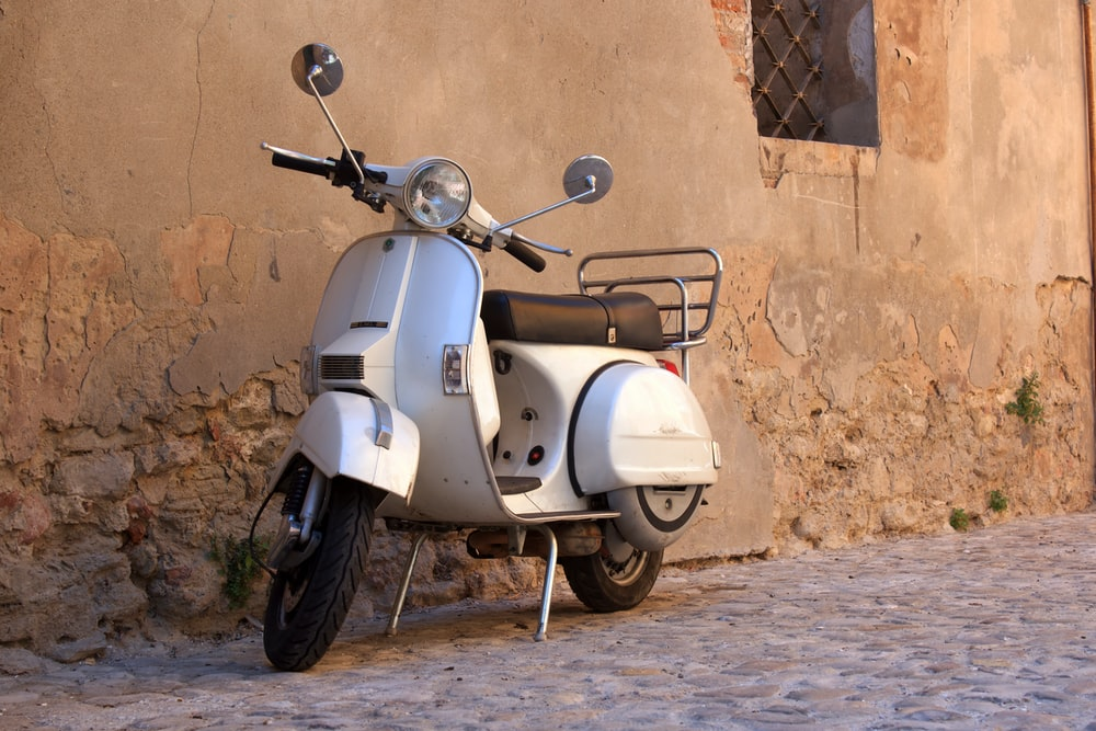 gray and black motor scooter parked beside brown concrete wall