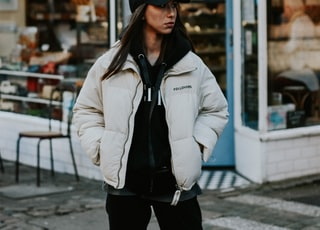woman in white jacket and black knit cap standing near store