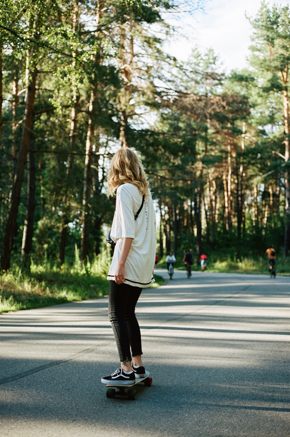 woman in white long sleeve shirt and black pants walking on road during daytime