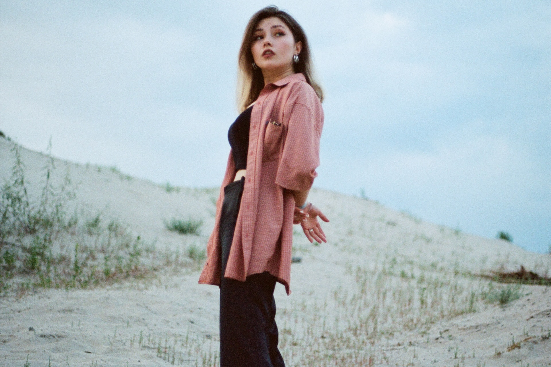 woman in pink scarf standing on brown field during daytime