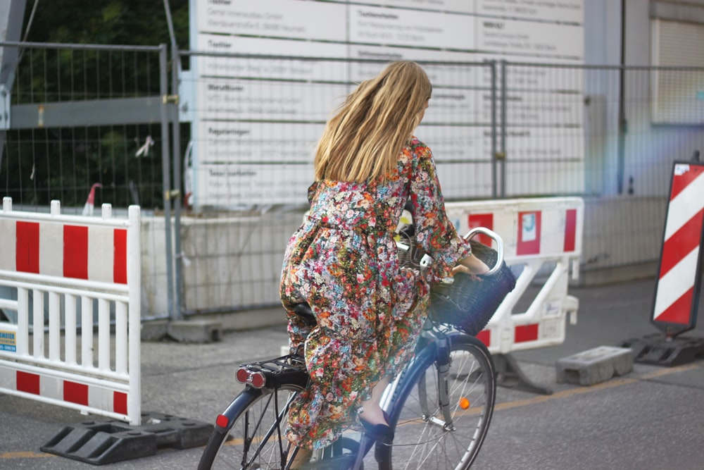 woman in white red and green floral long sleeve dress riding on bicycle during daytime