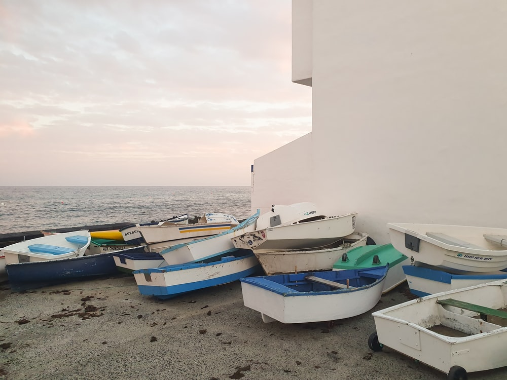 white and blue boats on beach during daytime