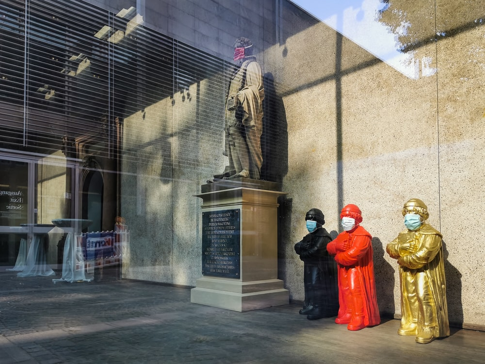 3 men in red robe standing near statue during daytime